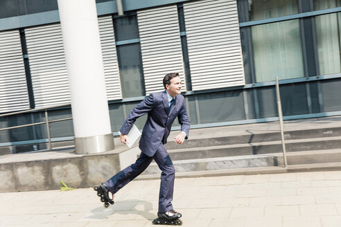Businessman inline skating in the city - MOEF01437