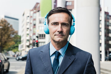 Portrait of businessman with headphones in the city - MOEF01440