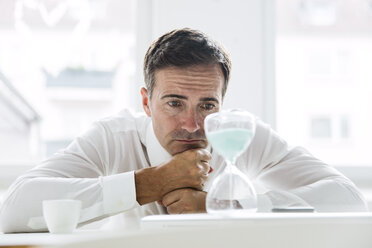 Serious businessman looking at hourglass on table in office - MOEF01452