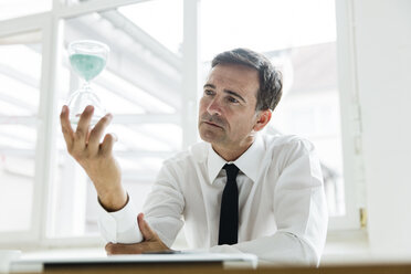 Serious businessman looking at hourglass in office - MOEF01455