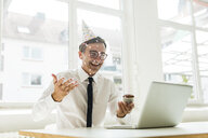 Laughing businessman with laptop celebrating birthday in office - MOEF01461