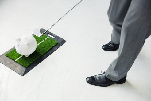 Close-up of businessman playing golf with piggy bank - MOEF01464