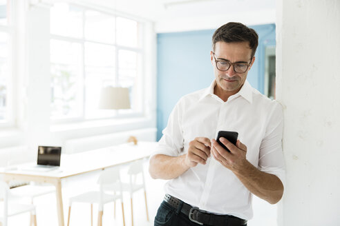 Businessman looking on cell phone in bright office - MOEF01467