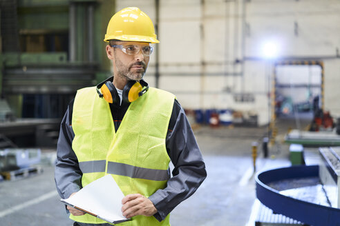 Man wearing protective workwear looking around in factory - BSZF00588