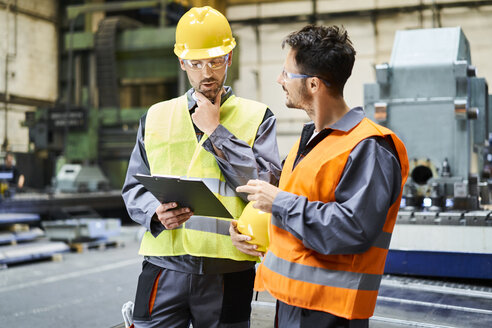 Two men wearing protective workwear holding clipboard and talking in factory - BSZF00591