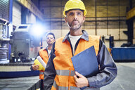 Two men wearing protective workwear looking around in factory - BSZF00594