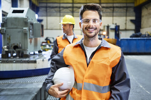 Portrait of smiling man wearing protective workwear in factory - BSZF00597