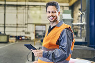 Portrait of smiling man holding tablet in factory - BSZF00600