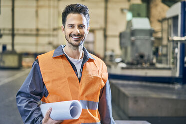 Portrait of smiling man holding blueprints in factory - BSZF00609