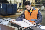 Man wearing protective workwear looking at blueprint in factory - BSZF00612