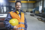 Portrait of smiling man wearing protective workwear in factory - BSZF00618