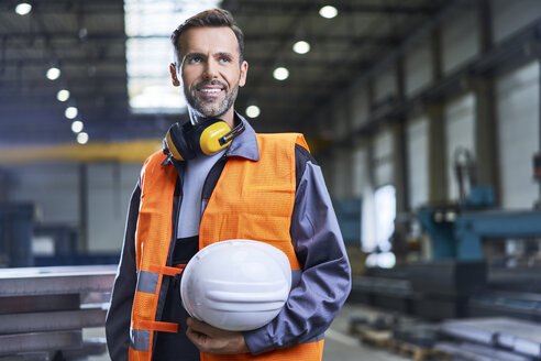 Portrait of smiling man wearing protective workwear in factory - BSZF00621