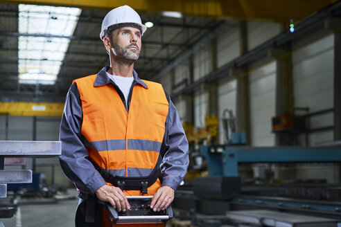 Portrait of man in factory operating machinery with remote console - BSZF00624