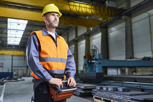 Portrait of man in factory operating machinery with remote console - BSZF00627