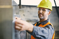 Portrait of confident man wearing protective workwear working in factory - BSZF00630