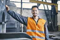 Portrait of smiling man wearing protective workwear in factory - BSZF00633