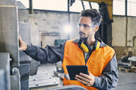 Man with tablet wearing protective workwear working in factory - BSZF00636