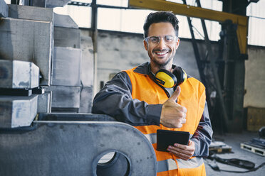 Portrait of smiling man wearing protective workwear showing thumbs up in factory - BSZF00639