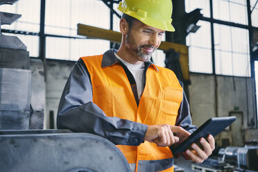 Smiling man wearing protective workwear using tablet in factory - BSZF00642