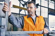 Man wearing protective workwear working in factory - BSZF00645