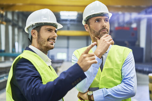 Two managers wearing protective workwear talking in factory - BSZF00648