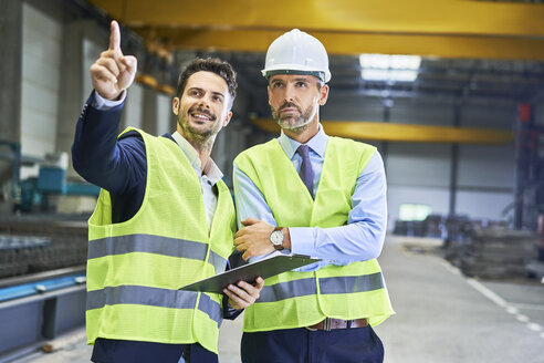 Two managers wearing protective workwear talking in factory - BSZF00651
