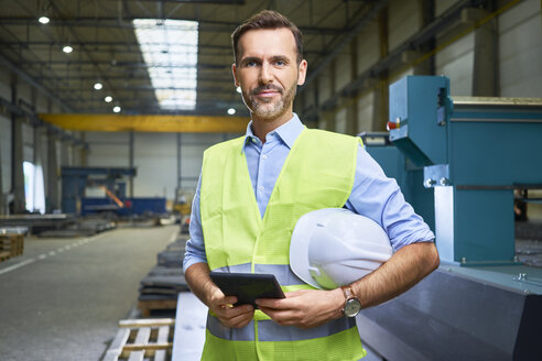 Portrait of confident man wearing shirt and safety vest in factory - BSZF00657