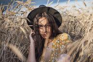 Portrait of young woman wearing hat sitting in corn field - VPIF00874