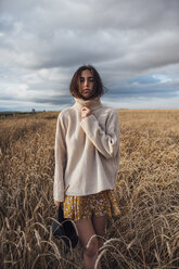 Portrait of young woman wearing oversized turtleneck pullover standing in corn field - VPIF00877