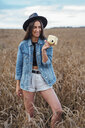 Portrait of laughing young woman wearing hat and denim jacket standing in a corn field with camera - VPIF00889
