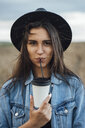 Portrait of young woman drinking beverage - VPIF00895