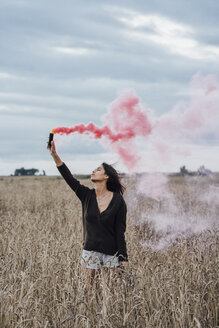 Young woman standing in a corn field with smoke torch - VPIF00898