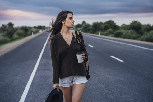 Portrait of hitchhiking young woman with backpack and beverage walking on lane - VPIF00904