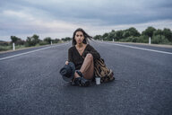 Portrait of hitchhiking young woman with backpack and beverage sitting on lane - VPIF00907
