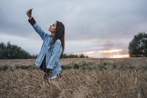 Young woman taking selfie with smartphone in a corn field at sunset - VPIF00910