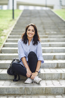 Portrait of smiling student sitting on stairs outdoors - JSMF00448