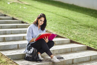 Student sitting on stairs outdoors taking notes in a notebook - JSMF00451