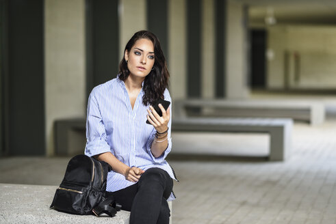 Portrait of pensive student with smartphone on campus - JSMF00457