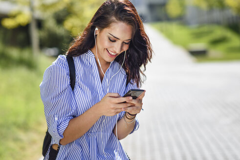Smiling student using smartphone and earphones - JSMF00472