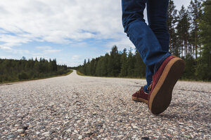 Finland, Lapland, feet of man walking on empty country road - KKAF02079