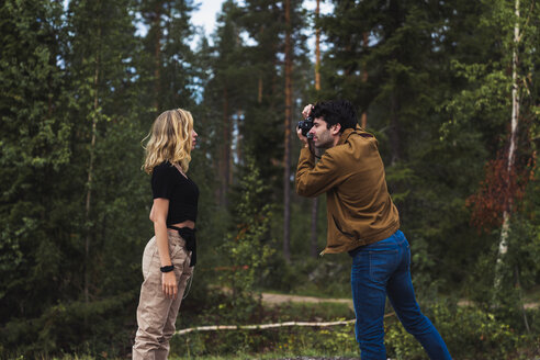Finland, Lapland, man taking picture of woman in rural landscape - KKAF02082
