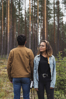 Finland, Lapland, man with camera and woman standing in rural landscape - KKAF02088