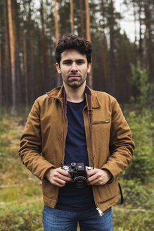 Finland, Lapland, portrait of young man holding camera in rural landscape - KKAF02091