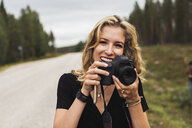 Finland, Lapland, portrait of happy young woman holding camera at country road - KKAF02094