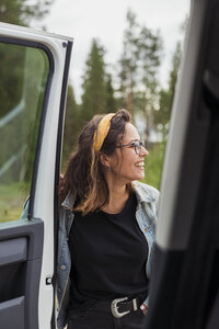 Finland, Lapland, happy young woman at a car in rural landscape - KKAF02097