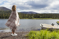 Finland, Lapland, woman wrapped in a blanket standing at the lakeside - KKAF02109