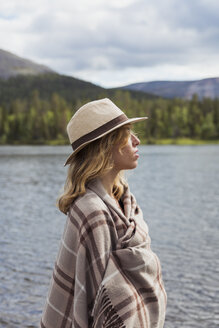 Finland, Lapland, woman wearing a hat wrapped in a blanket standing at the lakeside - KKAF02112