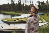 Finland, Lapland, woman wearing a hat wrapped in a blanket standing at the lakeside - KKAF02115