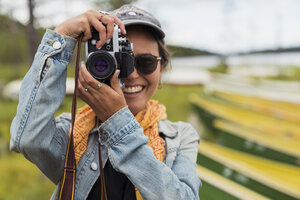 Finland, Lapland, portrait of smiling young woman taking picture with a camera at the lakeside - KKAF02121