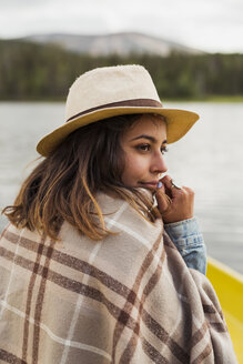 Finland, Lapland, woman wearing a hat on a boat on a lake - KKAF02124